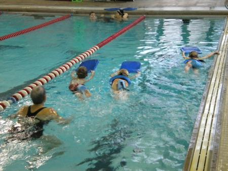 Children Learning to Kick Swim